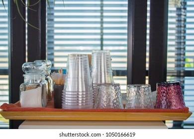 Empty glasses and sugar on wooden tray.