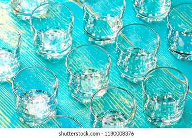 a lot of empty glasses for vodka on a blue table of wood, rows of glasses