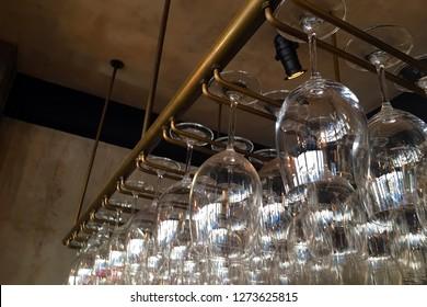 Empty glasses for wine above a bar rack. Restaurant, interior.