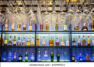 Empty glasses for wine above a bar rack with colorful and many of liquor bottles on the shelf.
