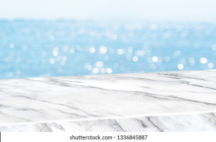 Empty glossy white marble table top with blur sky and sea boekh background,banner mock up template for display of product