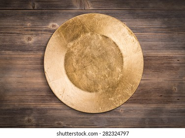 Empty gold plate on wooden background