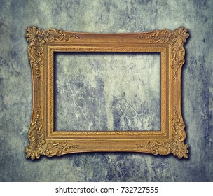 Empty golden baroque frame on grunge wall