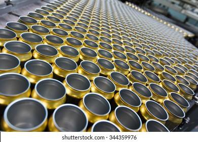 Empty golden beverage cans on the conveyor belt
