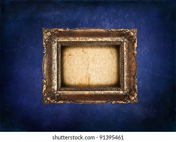 Empty golden frame on blue grunge wall