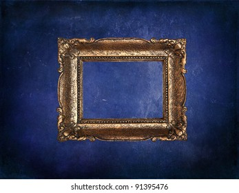 Empty golden frame on blue grunge wall
