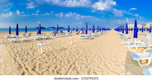 EMPTY GOLDEN SANDY BEACH WITH MANY PARASOLS AND DECKCHAIRS ATTRACTING TOURSITS AT MEDITERRANEAN SEA SIDE DURING BEAUTIFUL SUNNY SUMMER DAY, TOURISM CONCEPT