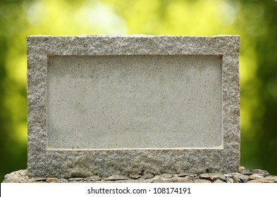 Empty granite signboard with border & frame. The granite is placed in natural outdoor settings showing vibrant green blurred background plants and sunlight effect.
