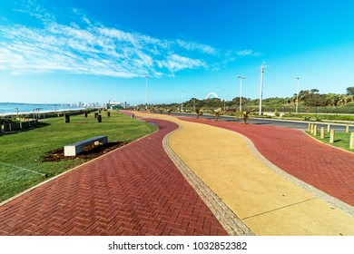 Empty grass lined paved promenade and sea against distant Durban city blue cloudy skyline coastal landscape in South Africa