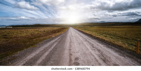 Empty gravel dirt road through countryside landscape and grass field. Nature off road travel trip for four-wheel-drive vehicle.