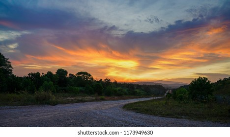 Empty gravel road against an orange sky at sunset
