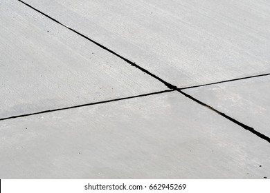 Empty gray concrete airport runway close-up with black sealant between concrete expansion joints.