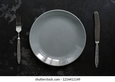 Empty gray plate and vintage fork and knife, black stone background. Top view.