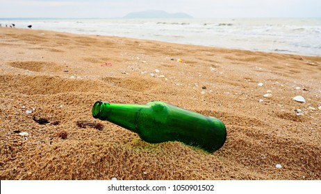 Empty green beer bottle on the beach. Concept of no garbage on beach.