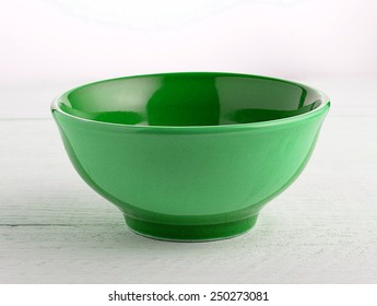 Empty green ceramic bowl on wood