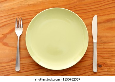empty green dish on the wooden table with fork and knife