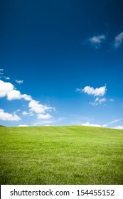 Empty green grass field and the blue sky with white clouds