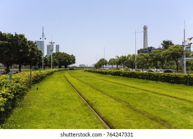 Empty green grass and track with buildings backgrounds