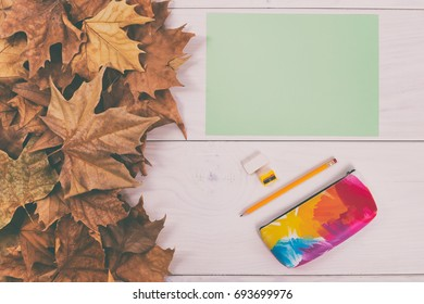 Empty green paper and school supplies on wooden table with autumn leaves.Back to school  Image is intentionally toned.