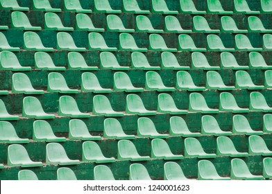 Empty green plastic spectators seats closeup on tennis court stand