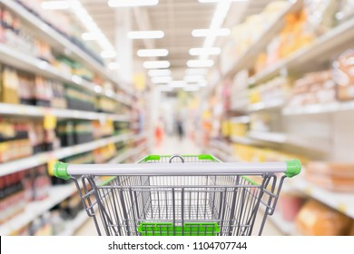 Empty green shopping cart with abstract blur supermarket discount store aisle and seasoning sauce product bottle shelves interior defocused background