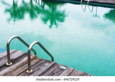 Empty green swimming pool with steel ladder and wooden floorboards.