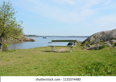 Empty green and white bench on a grassy hilltop above the water on Suomenlinna, a ferry sails past in the background