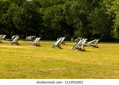 Empty green and white striped deck chairs under spring or summer sunshine in one of London park. UK