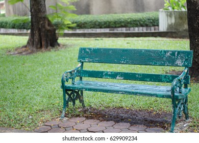 empty green wooden bench in garden. Alone and lonely concepts.