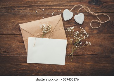 Empty greeting card and flowers with hearts on wooden background
