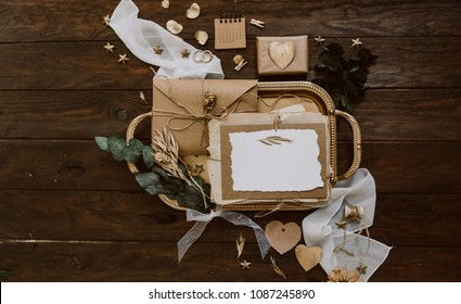 Empty greeting card with kraft envelope and gold decorations  on wooden background. Wedding concept. Top view, flat lay