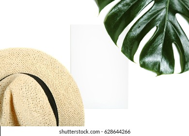 Empty greeting card mock up with straw hat and leaf of tropical palm leaf isolated on white background top view. Minimal styled feminine desktop.