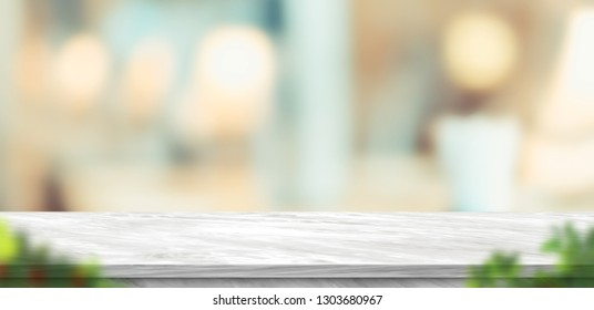 Empty grey marble table and blurred soft light table with foreground leaf in luxury restaurant with bokeh background. product display template.Business presentation