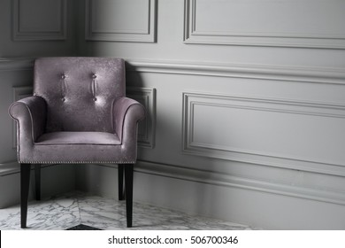 Empty grey single armchair in the corner of grey wall - front view with natural lighting