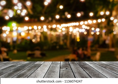 empty grey wooden floor or wooden terrace with abstract night light bokeh of night festival in garden, blurred background, copy space for display of product or object presentation, vintage color tone