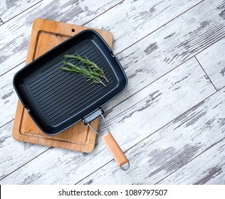 Empty grill pan with a sprig of rosemary over old wood floor, top view.