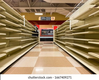Empty Grocery Store Aisle With No Products Available On Shelves After Selling Out