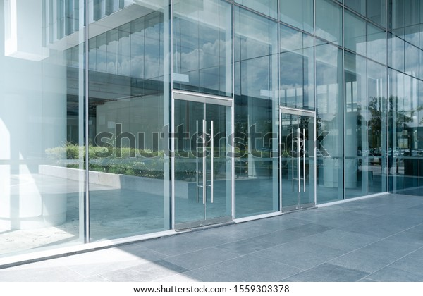 Empty ground in front of modern glass wall facade buildings .