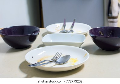Empty group of dirty white plates and black soup bowl with fork, spoon and waste food after eaten on marble table