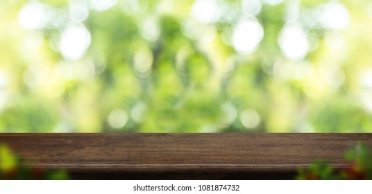 Empty grunge wood table top with blur tree in park with bokeh light at background,Mock up template for display of your design,Banner for advertise of product,panorama view.