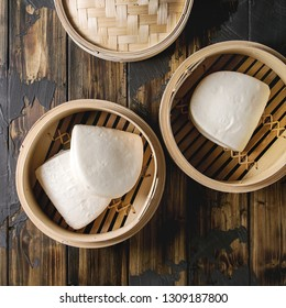 Empty gua bao steamed buns in opened bamboo steamer over dark wooden plank background. Flat lay, space. Asian fast food. Square image