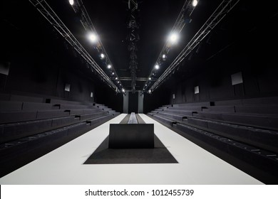 Empty hall for fashion shows with catwalk and rows of benches.
