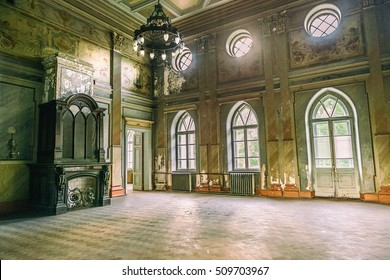 empty hall in Sharovsky Castle with chandelier, fireplace and arches on windows, Kharkiv region