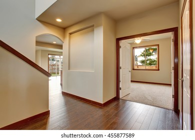 Empty hallway with hardwood floor, white walls. View of other room from the corridor