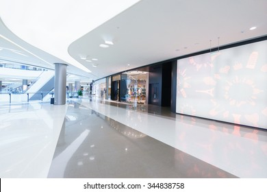 empty hallway with a huge billboard and abstract ceiling in modern shopping mall