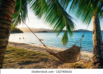 Empty hammock between two palm trees on the beach at sunset. Silhouette of couple in the background in sea. Holiday and vacation concept