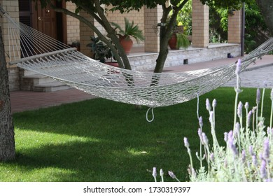 Empty hammock in the garden stretched between two trees.