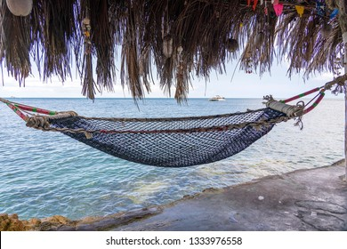 Empty hammock on beautiful tropical beach near blue sea water, Thailand, close up. Summer concept. Holiday travel.