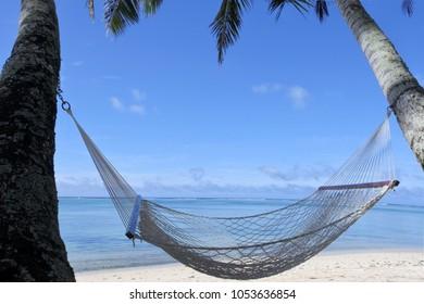 An empty hammock on Titikaveka beach in Rarotonga, Cook Islands.