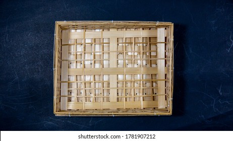 Empty Handmade Bamboo Basket on blue background, top view or directly above shooting